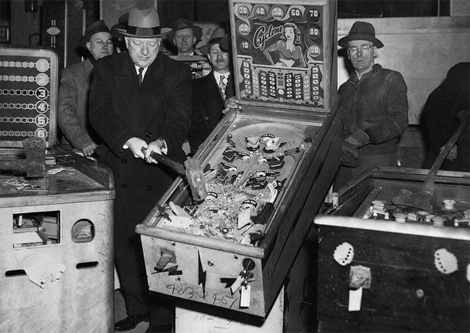 Mob Bosses trying to extort information out of a pinball machine.